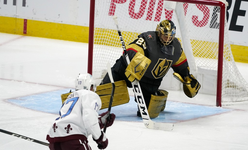Vegas Golden Knights goaltender Marc-Andre Fleury, back, makes a stick save of a shot by Colorado Avalanche center Tyson Jost in the first period of a...
