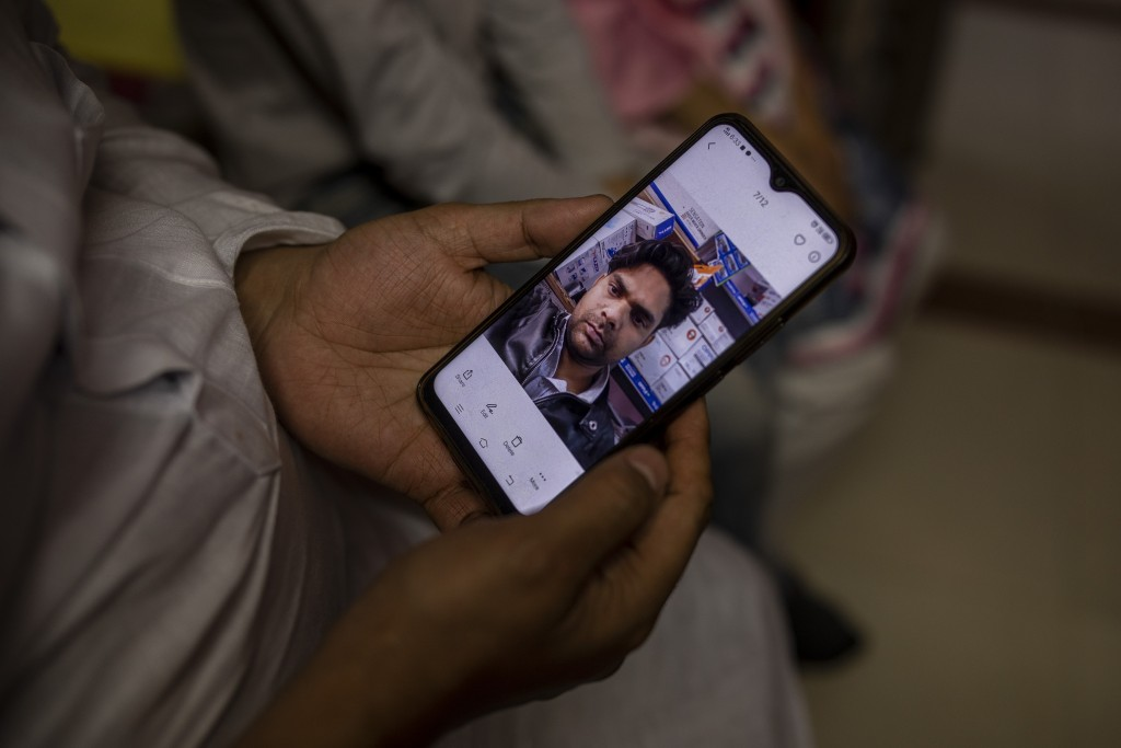 Haroon holds a mobile phone with a photograph of his 32 year-old brother who was shot and killed by his Hindu neighbors during the February 2020 commu...