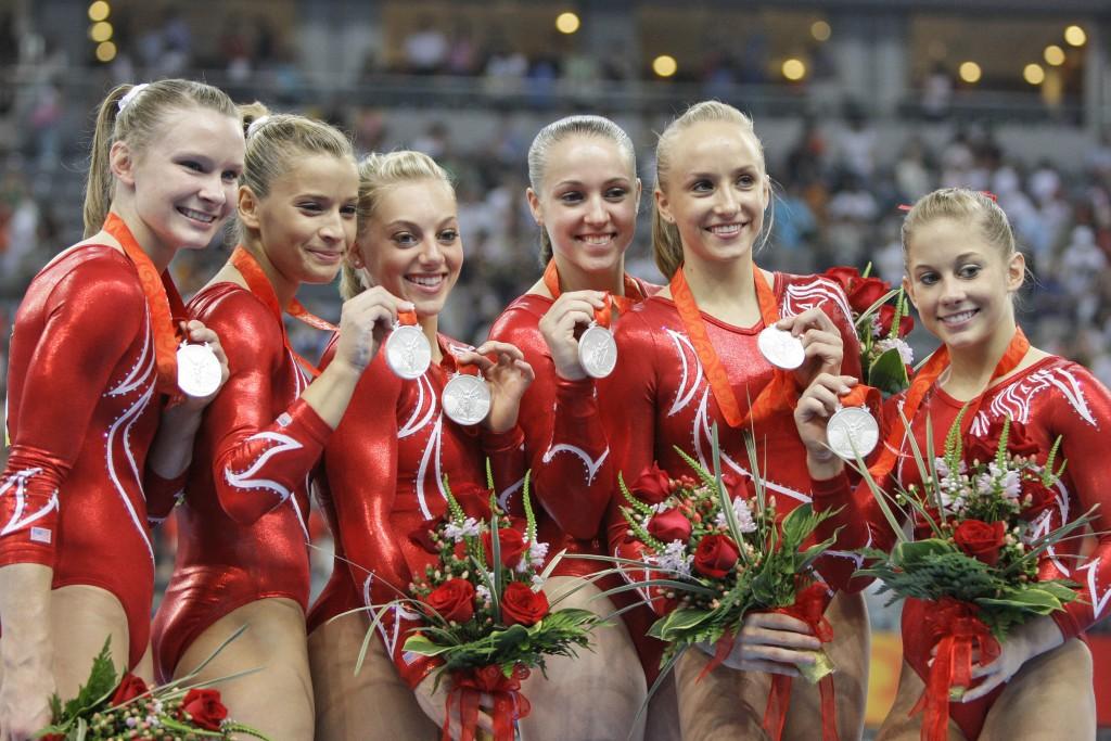 FILE - U.S. gymnasts, from left: Bridget Sloan, Alicia Sacramone, Samantha Peszek, Chellsie Memmel, Nastia Liukin, and Shawn Johnson pose with their s...
