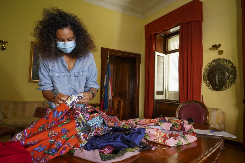 FILE - In this Aug. 13, 2020 file photo, fashion designer Stella Jean wears a face mask to curb he spread of COVID-19 as she holds fabrics during an i...