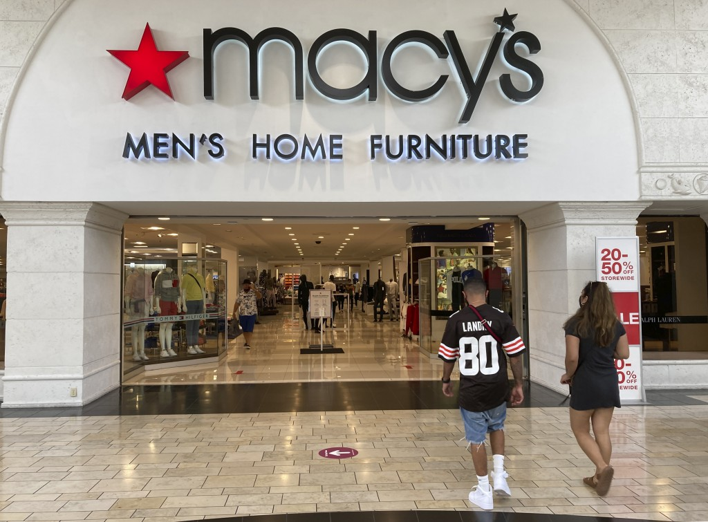 Shoppers walk into a Macy's department store Monday, Feb. 22, 2021, at Miami International Mall in Doral, Fla. Macy's is reporting a 52% drop in fisca...