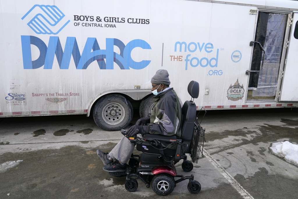 Thomas Washington, of Des Moines, Iowa, arrives at a Des Moines Area Religious Council mobile food pantry stop to pick up a Farmers to Families Food B...