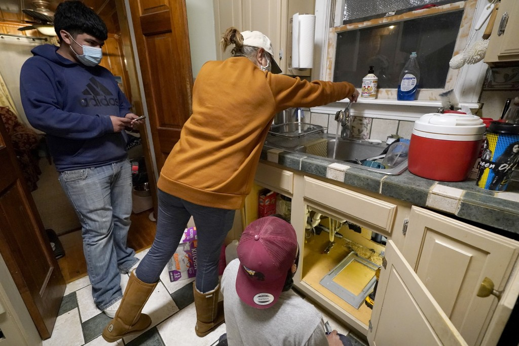 CORRECTS SPELLING OF LAST NAME TO VALERIO, NOT VALERIA - Roberto Valerio Jr., left, and his cousin Hector Valerio, right, look on as homeowner Nora Es...