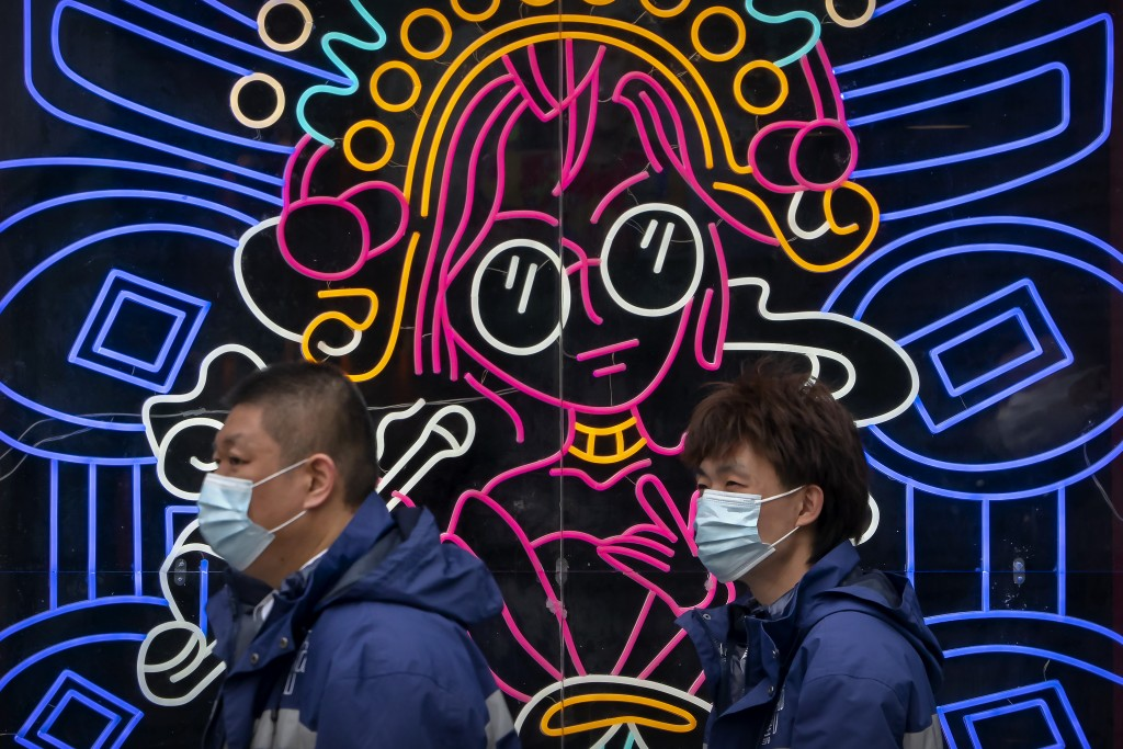 People wearing face masks to protect against the spread of the coronavirus walk past a display in the window of a commercial space in Beijing, Tuesday...