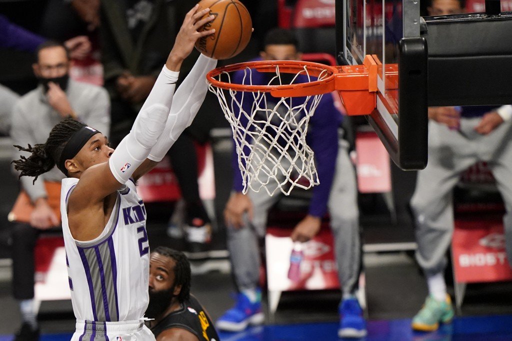 Sacramento Kings center Richaun Holmes, left, dunks the ball as Brooklyn Nets guard James Harden, right,  looks on from the floor during the first qua...