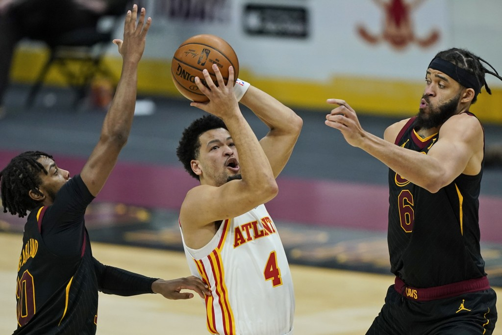 Atlanta Hawks' Skylar Mays (4) drives to the basket between Cleveland Cavaliers' Darius Garland (10) and JaVale McGee (6) in the second half of an NBA...