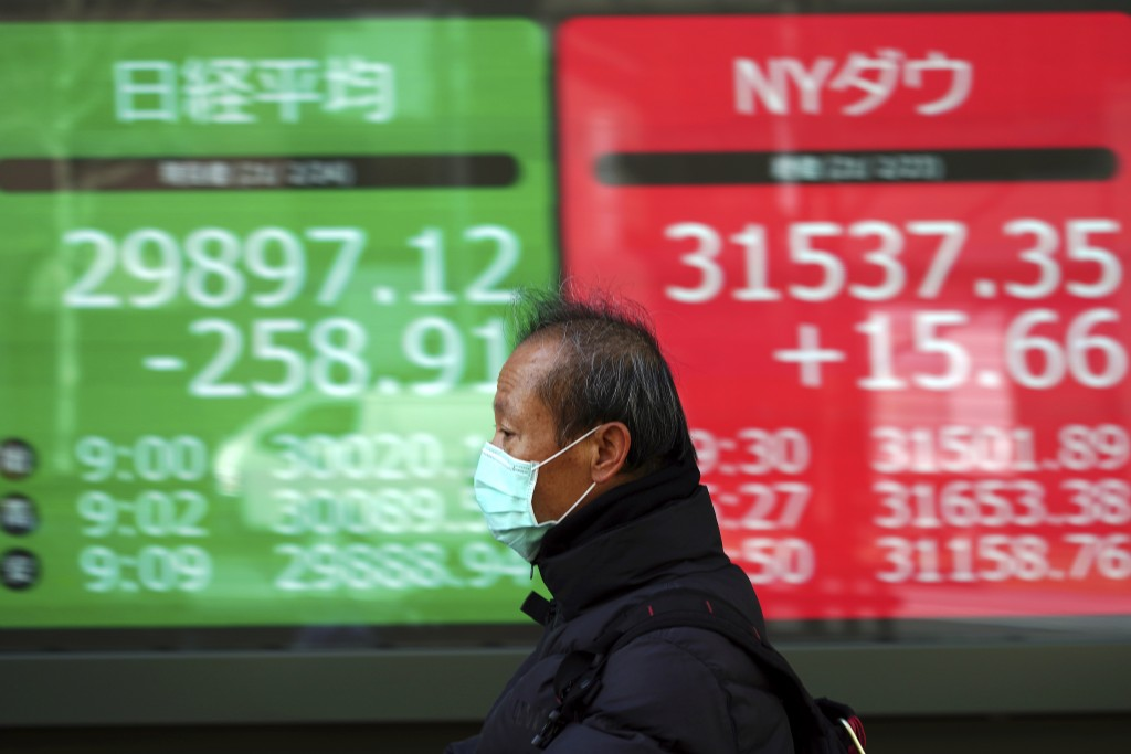 A man wearing a protective mask rides a bicycle in front of an electronic stock board showing Japan's Nikkei 225 and New York Dow indexes at a securit...