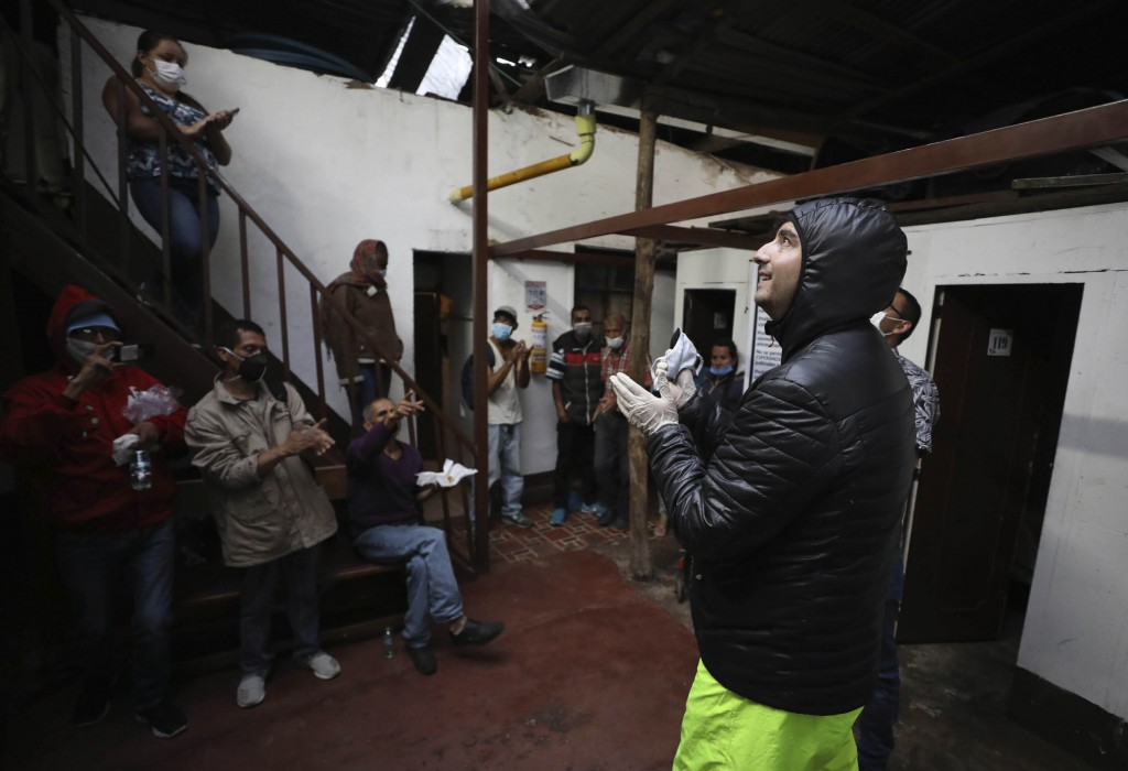 FILE - In this March 30, 2020 file photo, Emiliano Moscoso, right, talks to Venezuelan and Colombian people in a boarding house in Bogota, Colombia.  ...