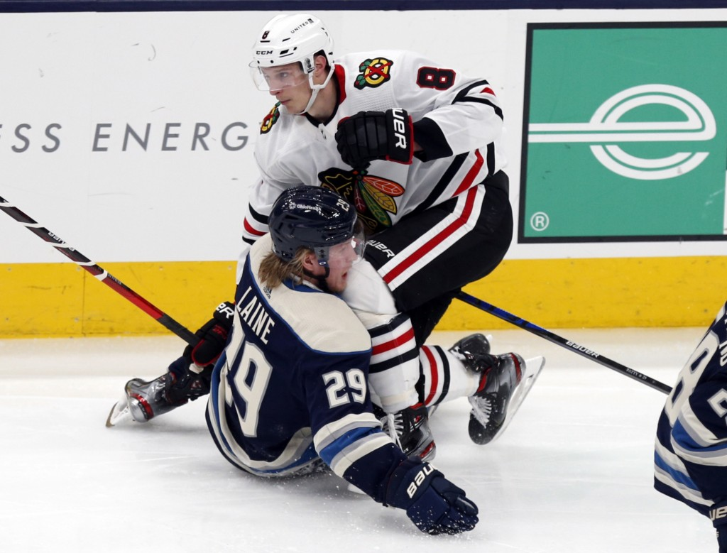 Chicago Blackhawks forward Dominik Kubalik, top, collides with Columbus Blue Jackets forward Patrik Laine during the second period of an NHL hockey ga...