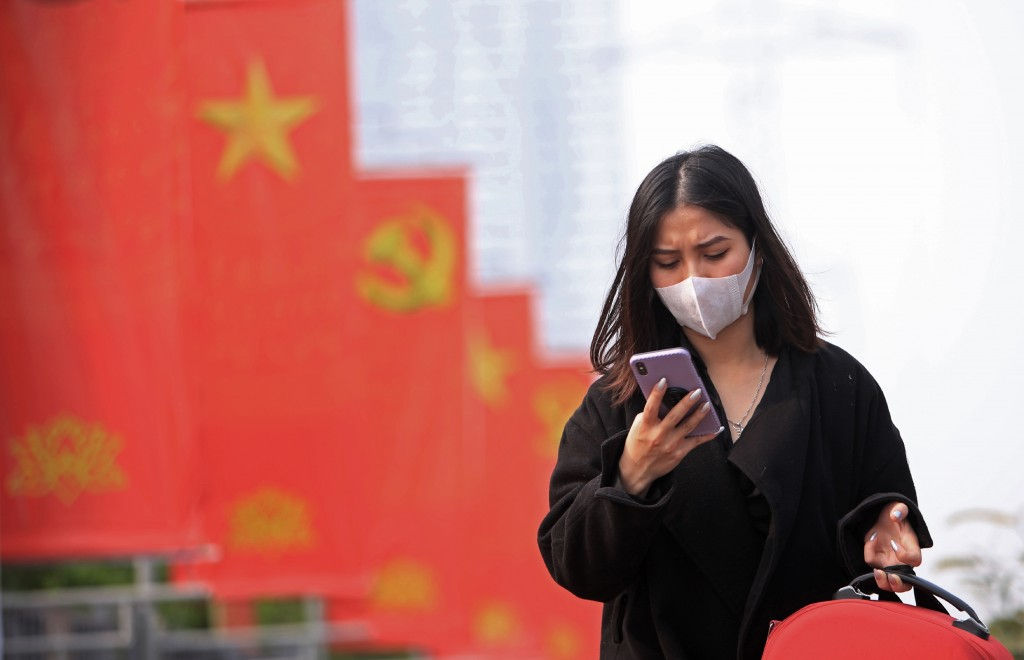 In this Jan. 23, 2021, file photo, a woman wearing face mask looks at her phone in Hanoi, Vietnam. Amnesty International has found that a hacking grou...