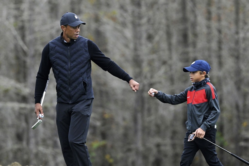 FILE - Tiger Woods, left, gives his son Charlie a fist bump after Charlie made a putt on the 12th green during a practice round of the Father Son Chal...