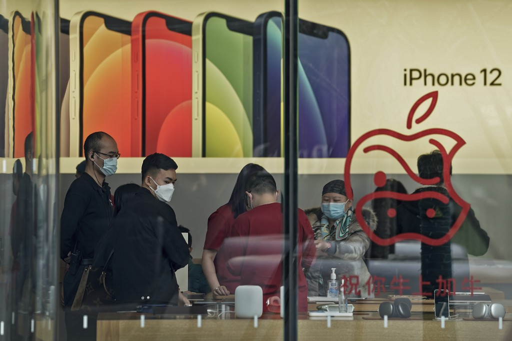 People wearing face masks to help curb the spread of the coronavirus look at iPad devices at an Apple store at the capital city's popular shopping mal...