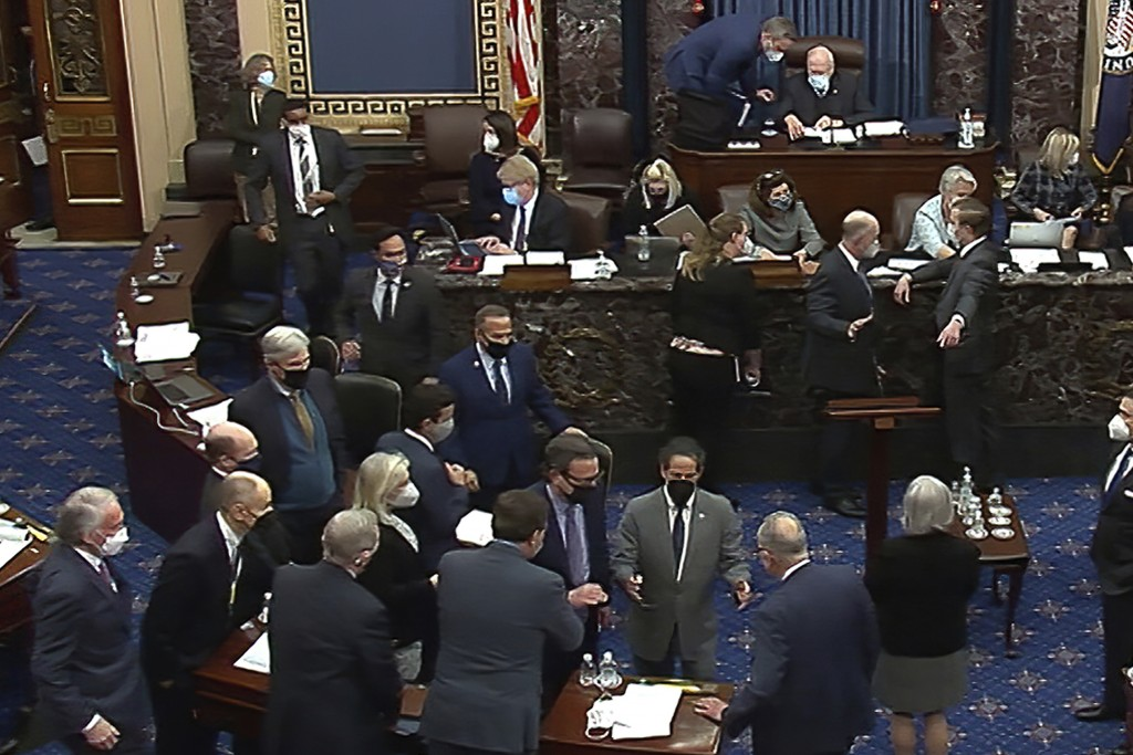 In this Feb. 10, 2021, image from video, Senate parliamentarian Elizabeth MacDonough, seated in the back second row third from right, talks as senator...