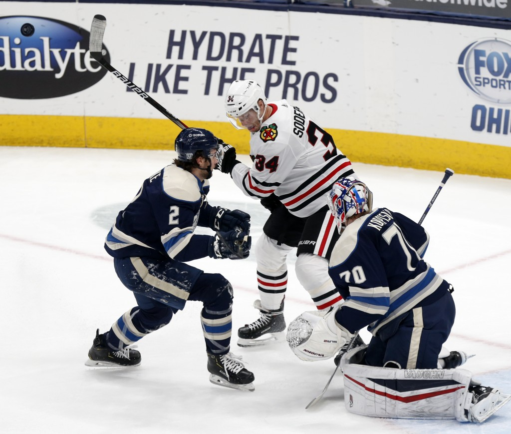 Chicago Blackhawks forward Carl Soderberg, center, works for the puck between Columbus Blue Jackets defenseman Andrew Peeke, left, and goalie Joonas K...