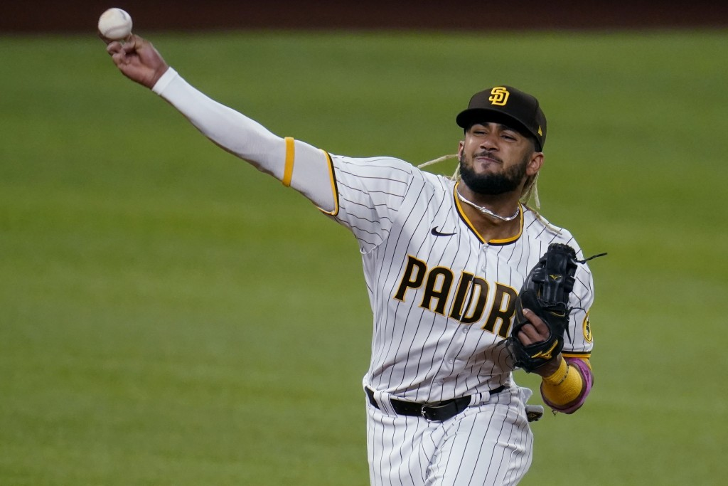 FILE - In this Oct. 8, 2020, file photo, San Diego Padres' Fernando Tatis Jr. throws to first for the out on Los Angeles Dodgers' Mookie Betts during ...