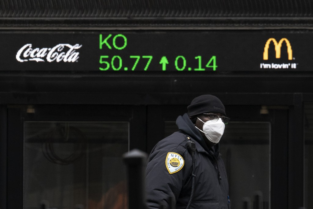 A security guard walks by a stock ticker displaying the cost of Coca-Cola shares at the New York Stock Exchange, Tuesday, Feb. 23, 2021. (AP Photo/Mar...