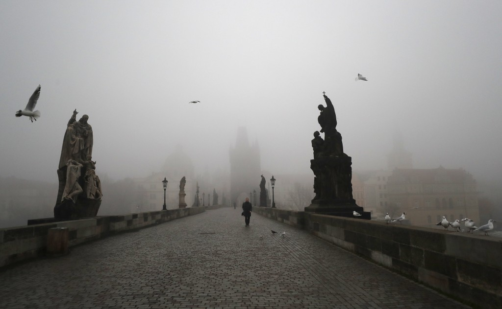 A man walks across the medieval Charles Bridge in Prague, Czech Republic, Wednesday, Feb. 24, 2021. The Czech government has decided to further tighte...