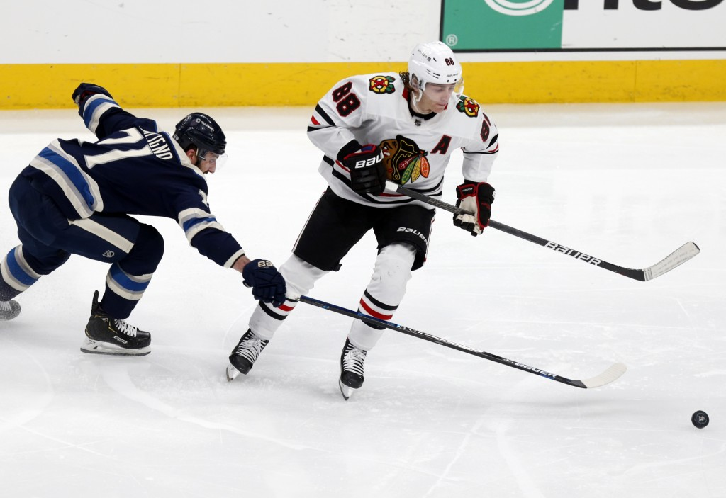 Chicago Blackhawks forward Patrick Kane, right, chases the puck next to Columbus Blue Jackets forward Nick Foligno during the second period of an NHL ...