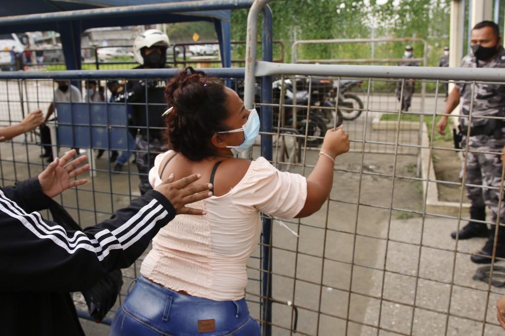 A relative of an inmate grabs a fence outside the Centro de Privación de Libertad Zona 8 prison where riots broke out in Guayaquil, Ecuador, Tuesday, ...