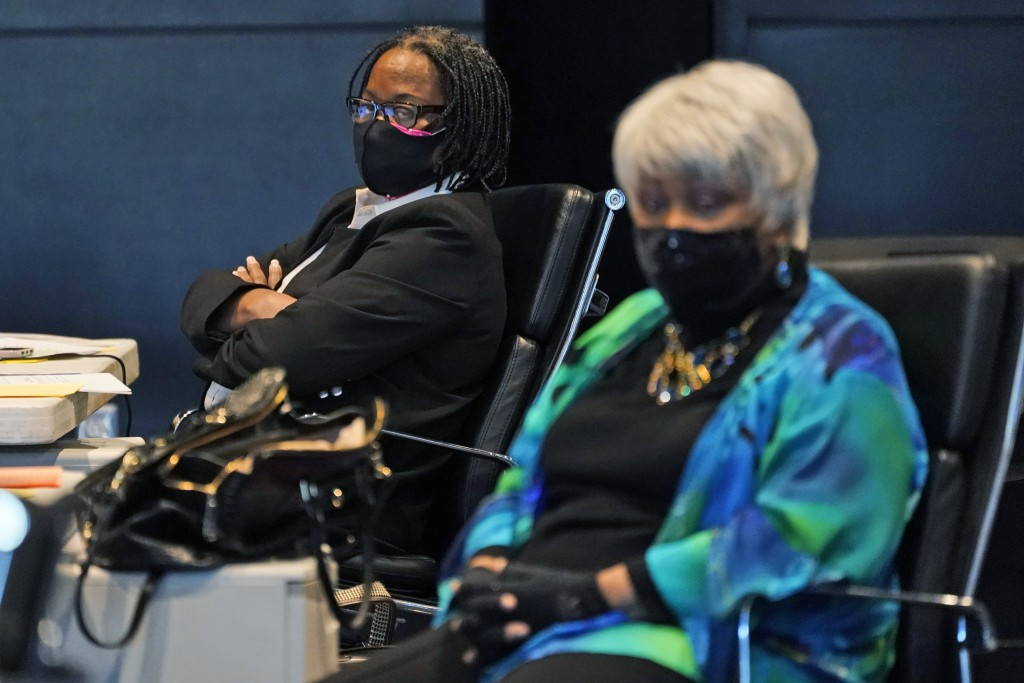 Virginia State Sen. Maime Locke, D-Hampton, left, listens along with Sen. Louise Lucas, D-Portsmouth, right, during debate on a bill calling for the r...