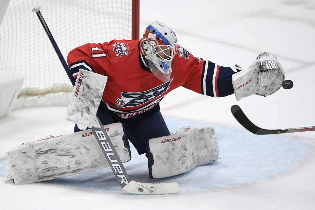 Washington Capitals goaltender Vitek Vanecek (41) reaches to catch the puck during the second period of an NHL hockey game against the Pittsburgh Peng...