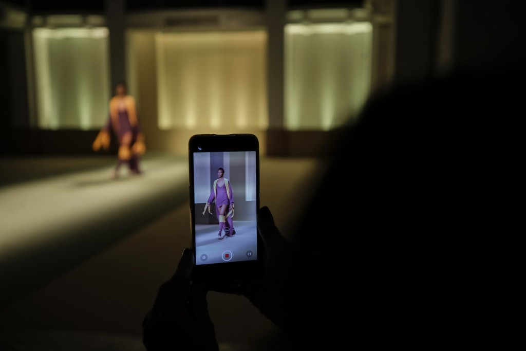 A model seen through the screen of a smartphone wears a creation designed by fashion designer Gisele Claudia, as part of the Black Lives Matter Fall/W...