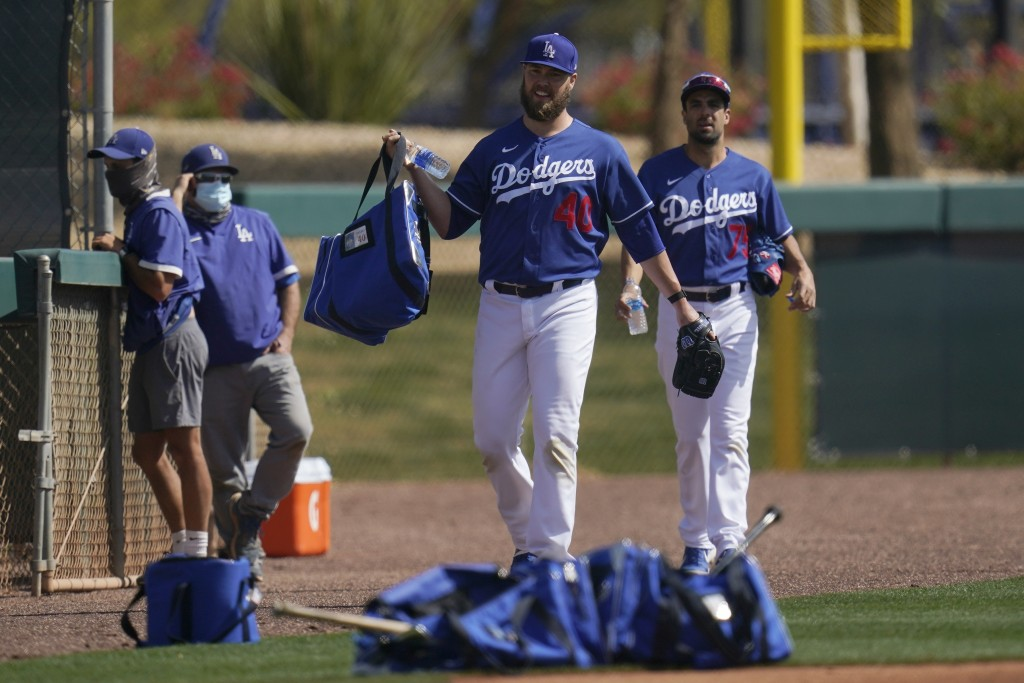 Los Angeles Dodgers pitchers Jimmy Nelson and Scott Alexander (75) make their way on to a new practice field during a spring training baseball practic...