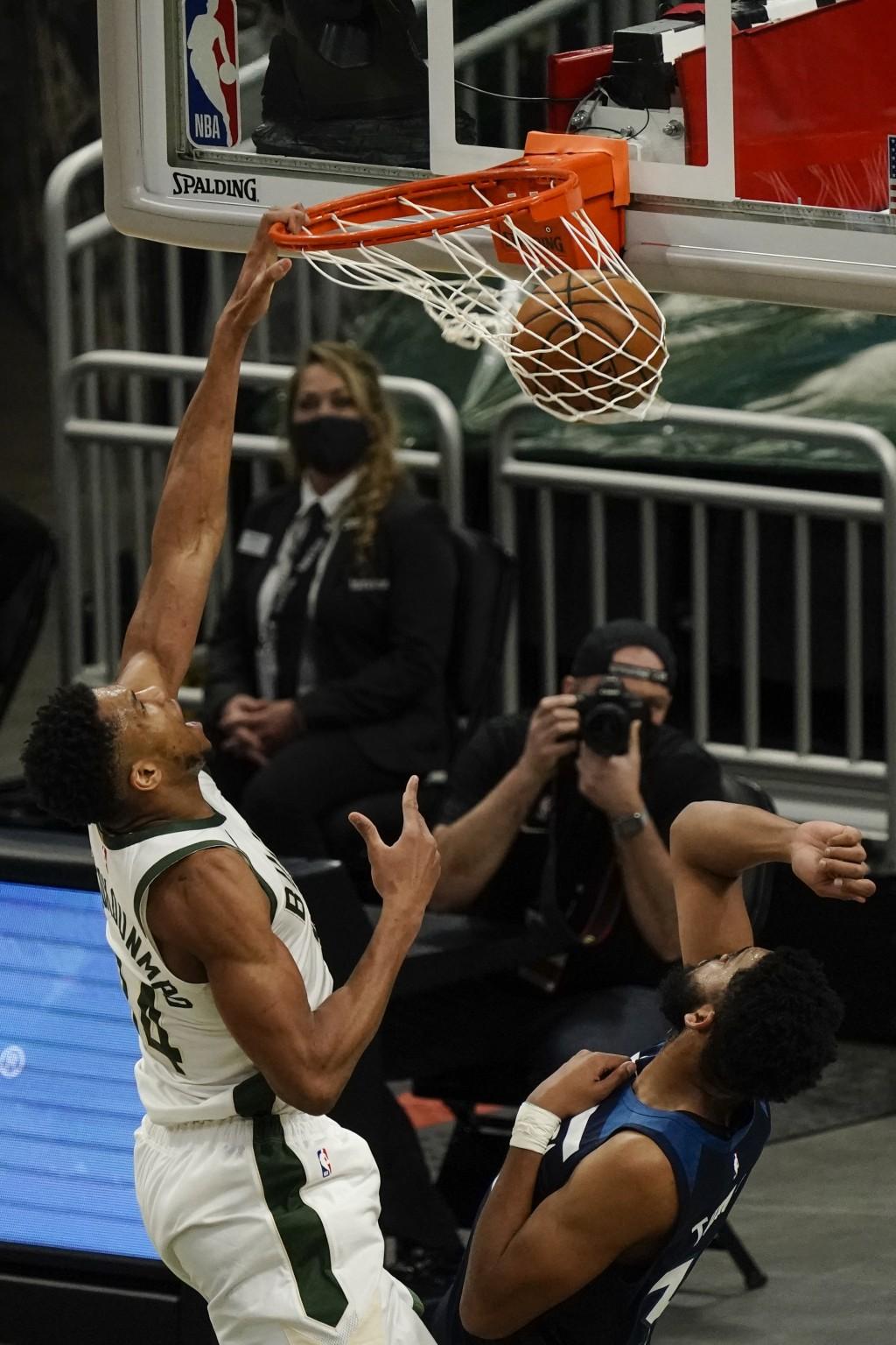 Milwaukee Bucks' Giannis Antetokounmpo dunks over Minnesota Timberwolves' Karl-Anthony Towns during the first half of an NBA basketball game Tuesday, ...