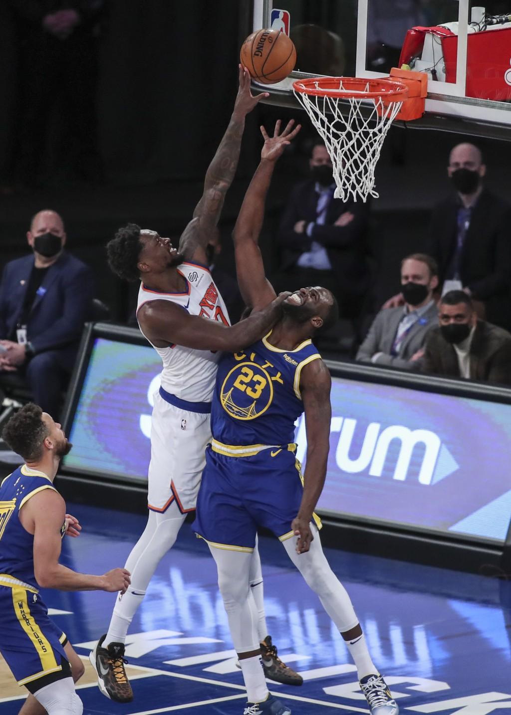 New York Knicks forward Julius Randle shoots over Golden State Warriors forward Draymond Green (23) during the second quarter of an NBA basketball gam...