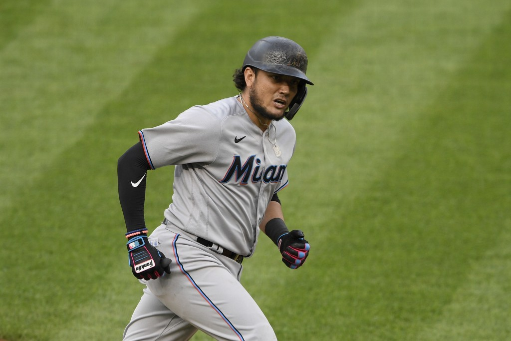 FILE - Miami Marlins' Miguel Rojas reacts as he rounds the bases on his three-run home run during a baseball game against the Washington Nationals in ...