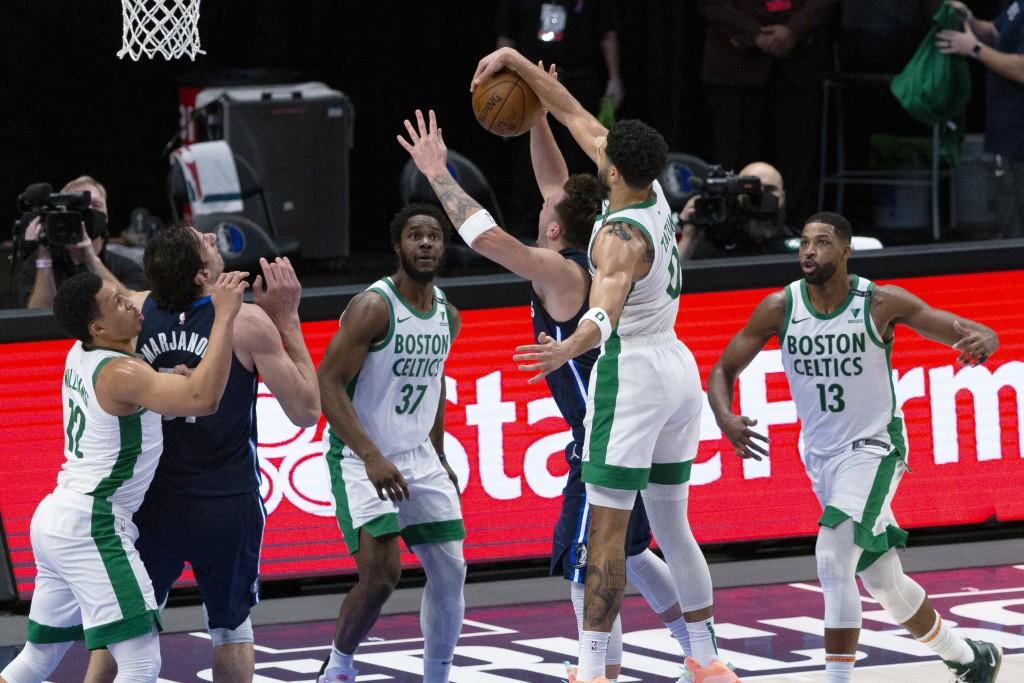Boston Celtics forward Jayson Tatum (0) blocks Dallas Mavericks guard Luka Doncic (77) on a shot attempt during the first half of an NBA basketball ga...
