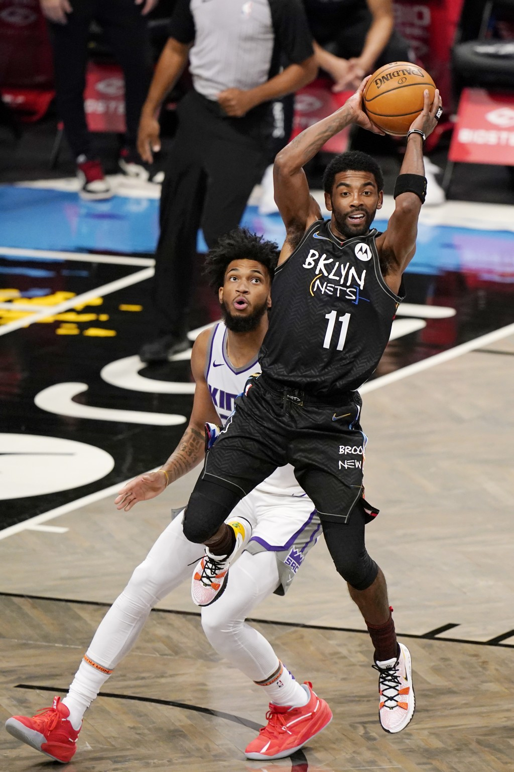 Sacramento Kings forward Marvin Bagley III, left,  looks on as Brooklyn Nets guard Kyrie Irving, right, passes during the first quarter of an NBA bask...