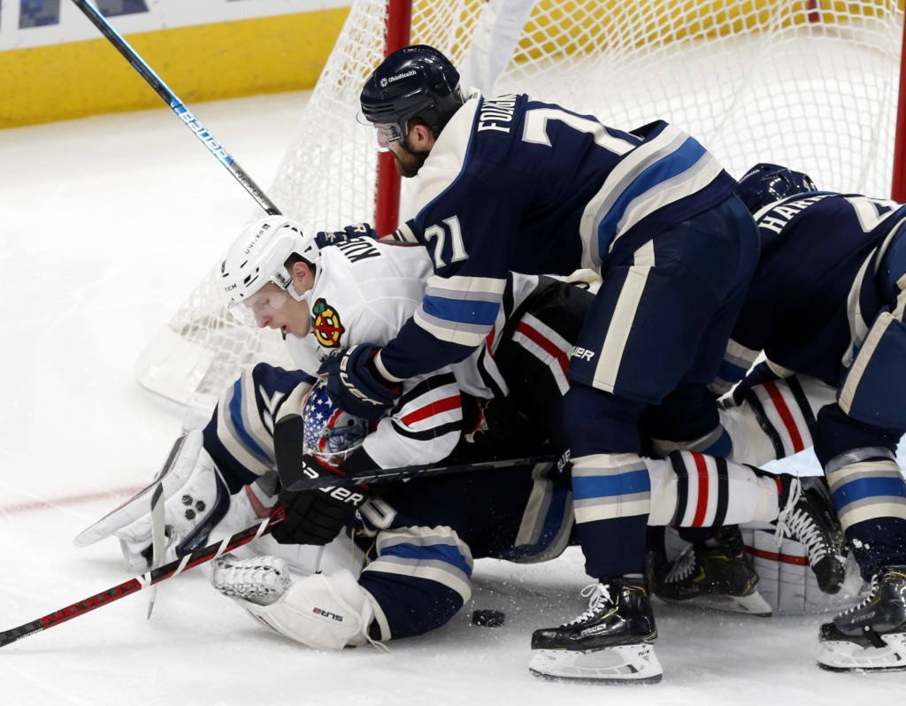 Columbus Blue Jackets forward Nick Foligno, top, checks Chicago Blackhawks forward Dominik Kubalik against Blue Jackets goalie Joonas Korpisalo during...