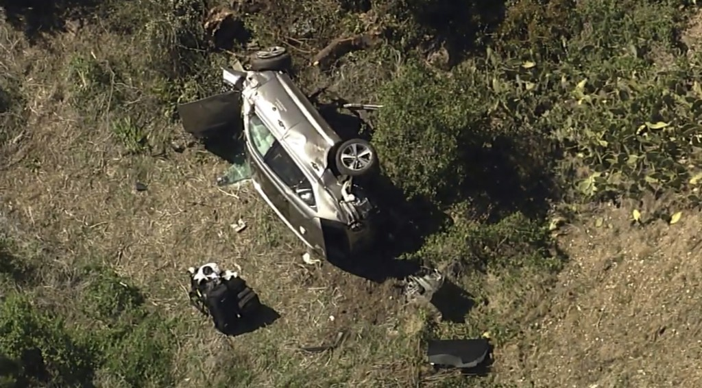In this aerial image take from video provided by KABC-TV, a vehicle rest on its side after a rollover accident involving golfer Tiger Woods along a ro...