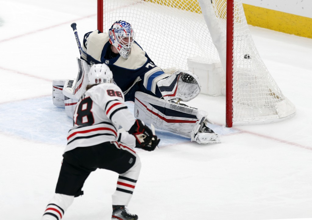 Chicago Blackhawks forward Patrick Kane, left, scores past Columbus Blue Jackets goalie Joonas Korpisalo during the first period of an NHL hockey game...