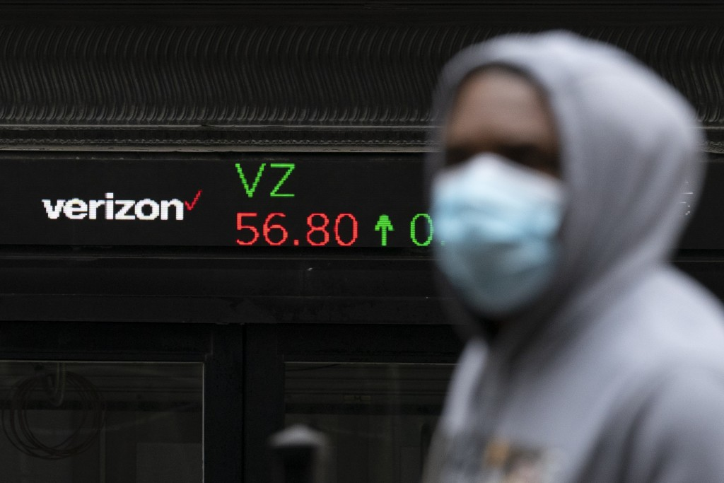 A man walks by a stock ticker displaying the cost of Verizon shares at the New York Stock Exchange, Tuesday, Feb. 23, 2021. (AP Photo/Mark Lennihan)