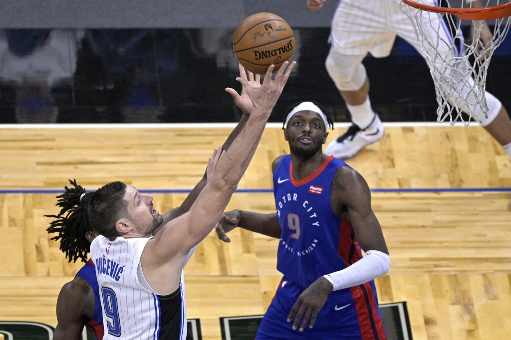 Orlando Magic center Nikola Vucevic (9) goes up for a shot in front of Detroit Pistons center Isaiah Stewart, obscured, and forward Jerami Grant (9) d...