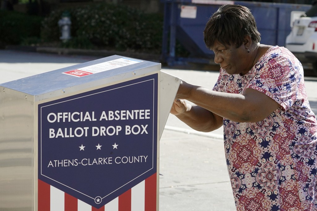 FILE - In this Oct. 19, 2020 file photo, a voter drops their ballot off during early voting in Athens, Ga. After record turnout led to stunning GOP lo...