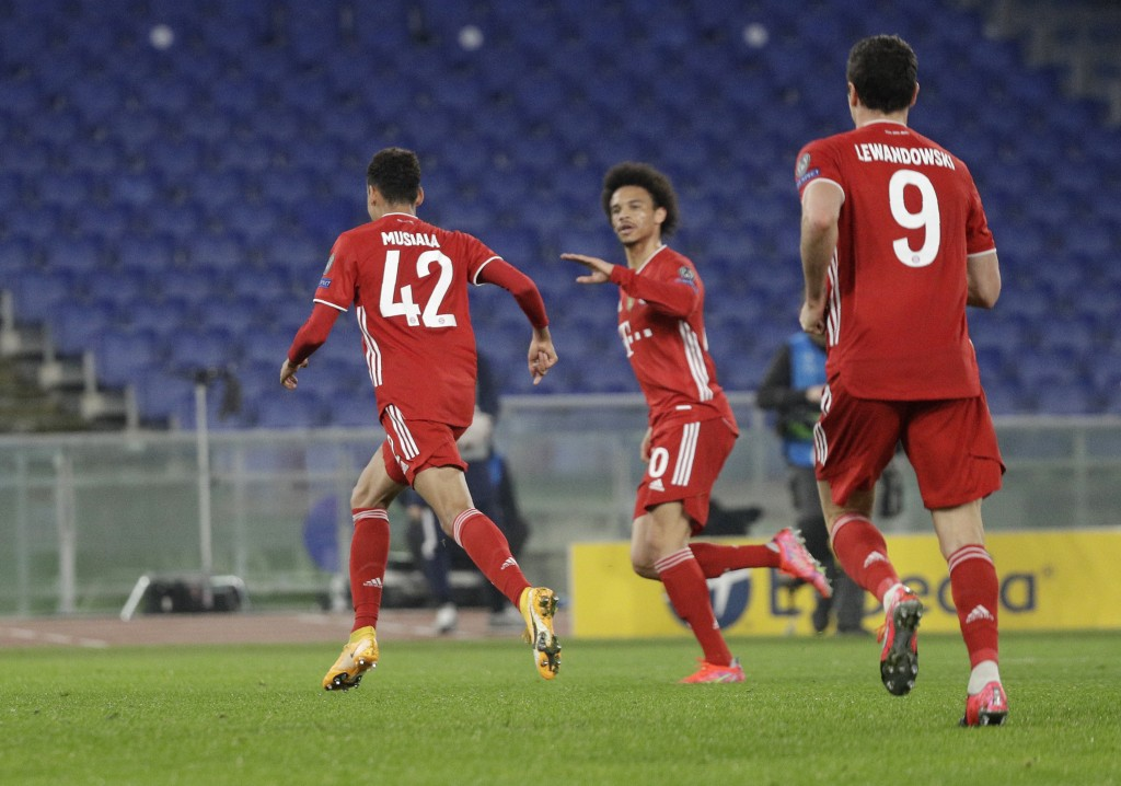 Bayern's Jamal Musiala, left, celebrates with his teammates after scoring his side's second goal during the Champions League round of 16 first leg soc...