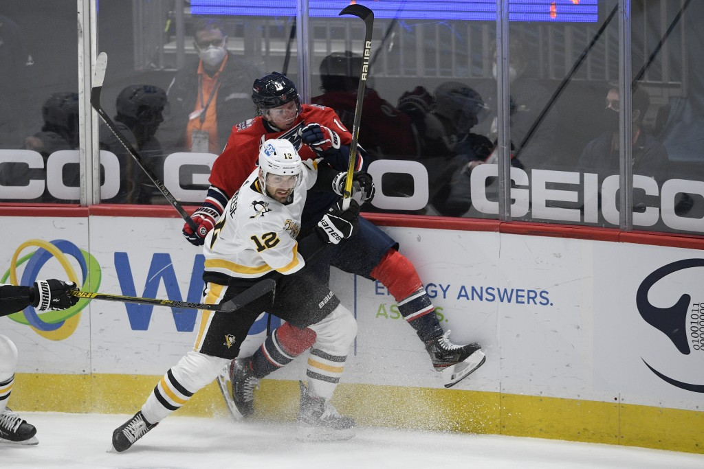 Pittsburgh Penguins center Zach Aston-Reese (12) checks Washington Capitals center Nicklas Backstrom (19) into the boards during the second period of ...
