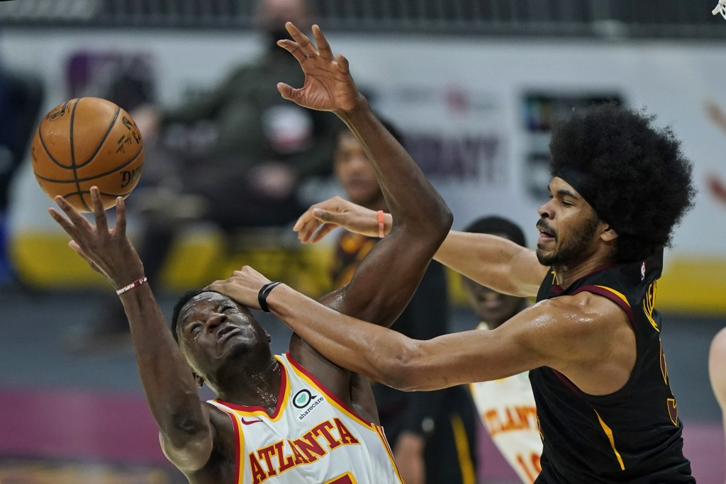 Atlanta Hawks' Clint Capela, left, and Cleveland Cavaliers' Jarrett Allen battle for a loose ball in the first half of an NBA basketball game, Tuesday...