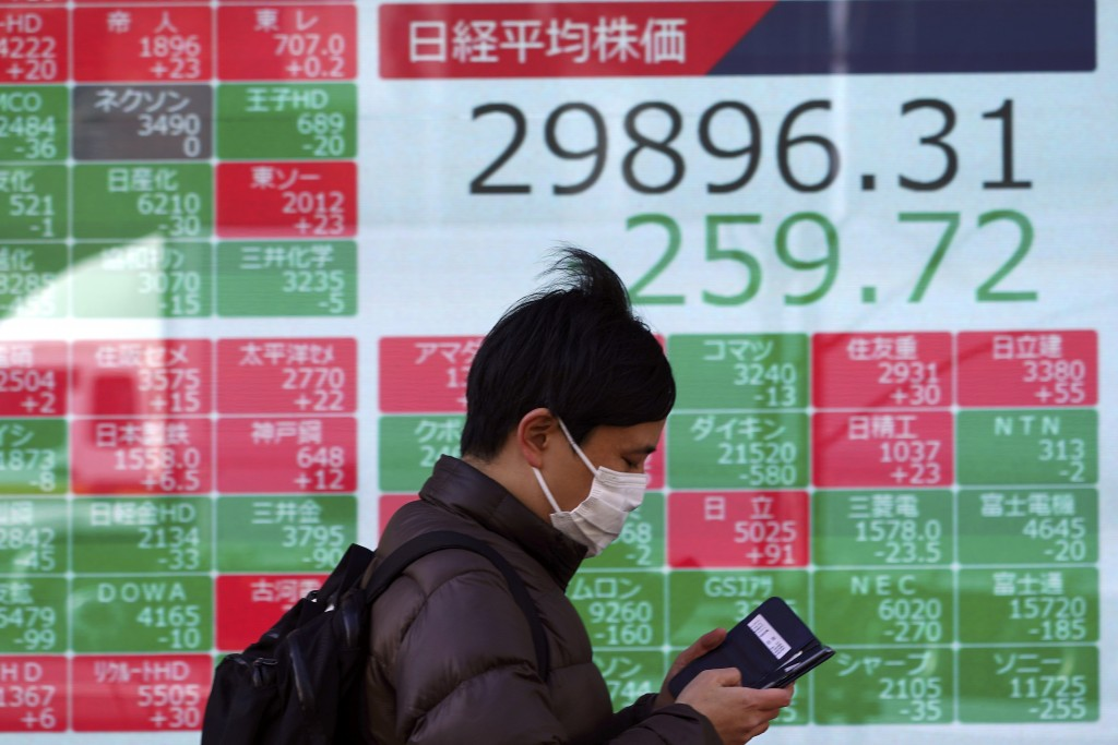 A man wearing a protective mask walks in front of an electronic stock board showing Japan's Nikkei 225 index at a securities firm Wednesday, Feb. 24, ...
