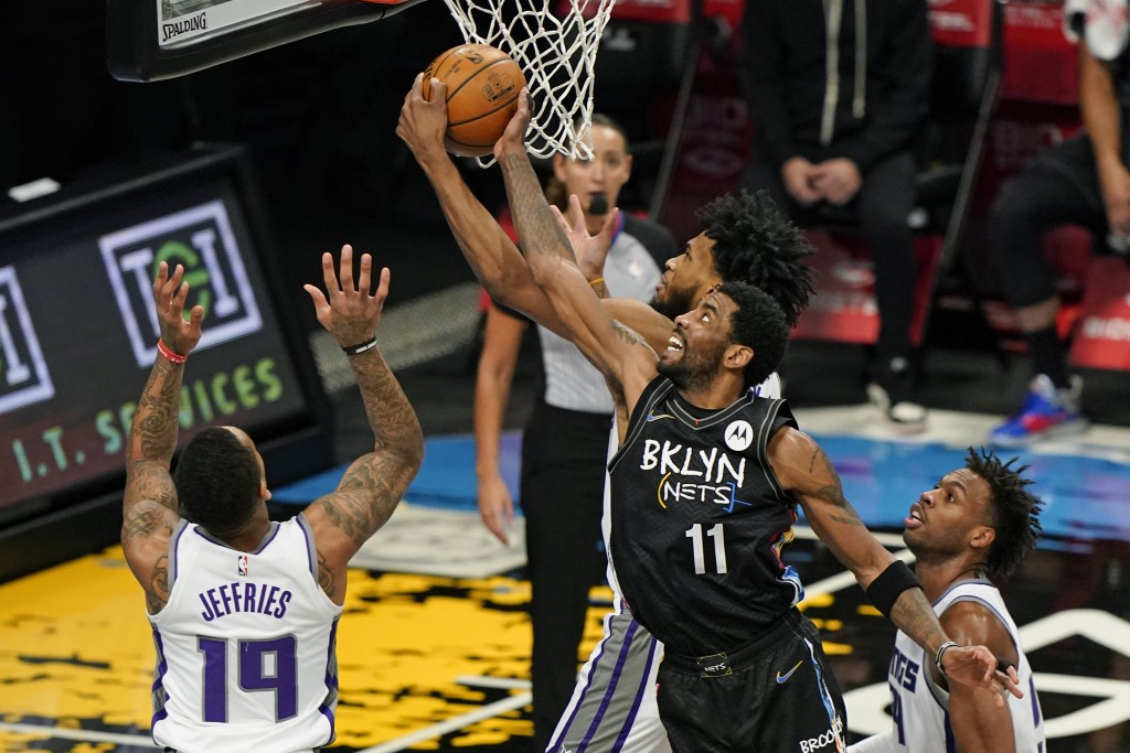 Sacramento Kings forward Marvin Bagley III tries to steal the ball from Brooklyn Nets guard Kyrie Irving (11) during the first half of an NBA basketba...