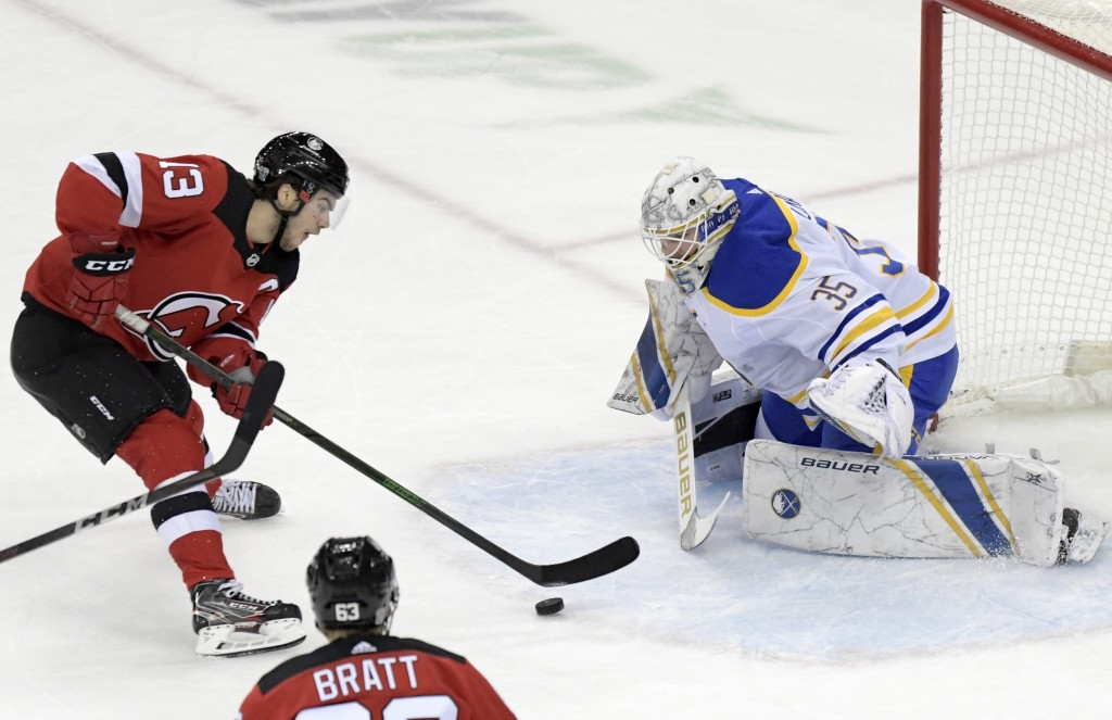 New Jersey Devils center Nico Hischier (13) skates in on Buffalo Sabres goaltender Linus Ullmark (35) during the second period of an NHL hockey game T...