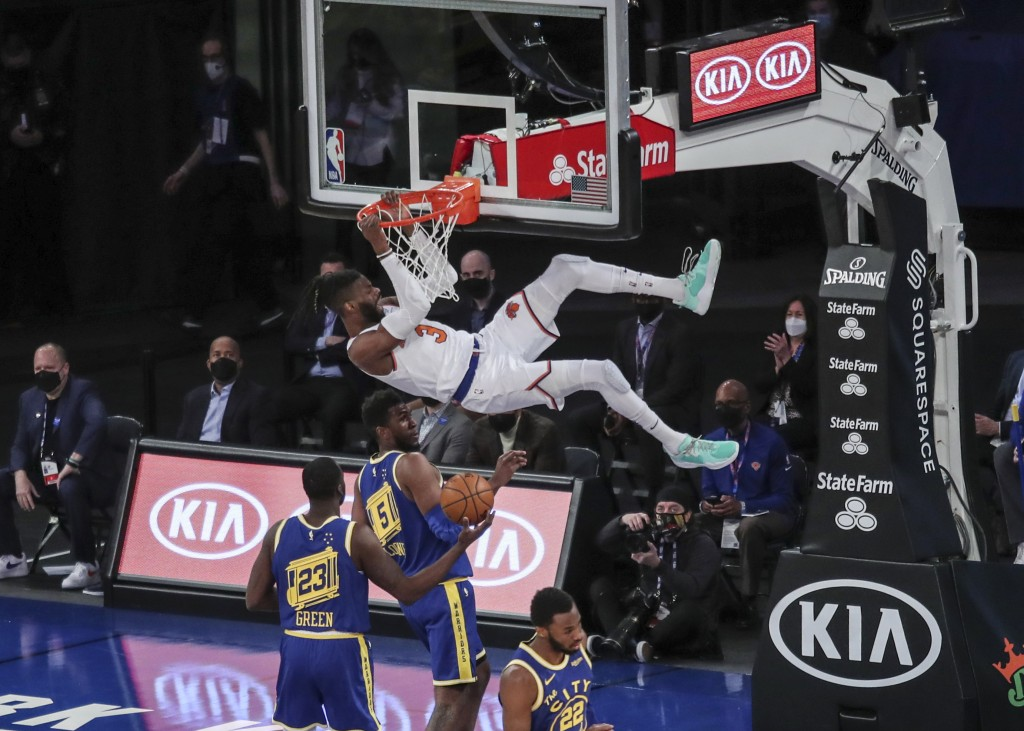 New York Knicks center Nerlens Noel hangs from the rim after a dunk against the Golden State Warriors during the first quarter of an NBA basketball ga...