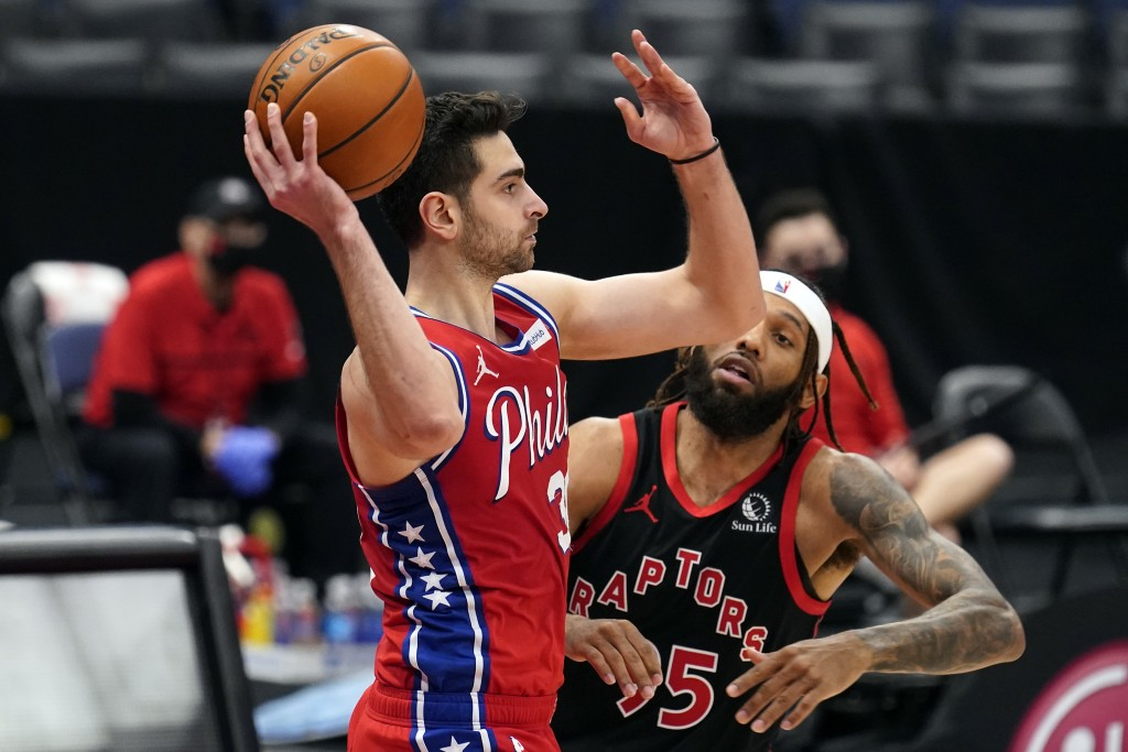 Philadelphia 76ers guard Furkan Korkmaz (30) looks to pass in front of Toronto Raptors forward DeAndre' Bembry (95) during the second half of an NBA b...