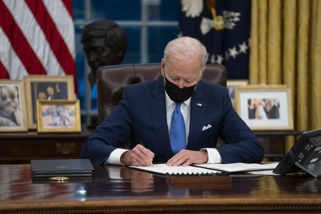 FILE - In this Feb. 2, 2021, file photo, President Joe Biden signs an executive order, in the Oval Office of the White House, in Washington.  Biden is...