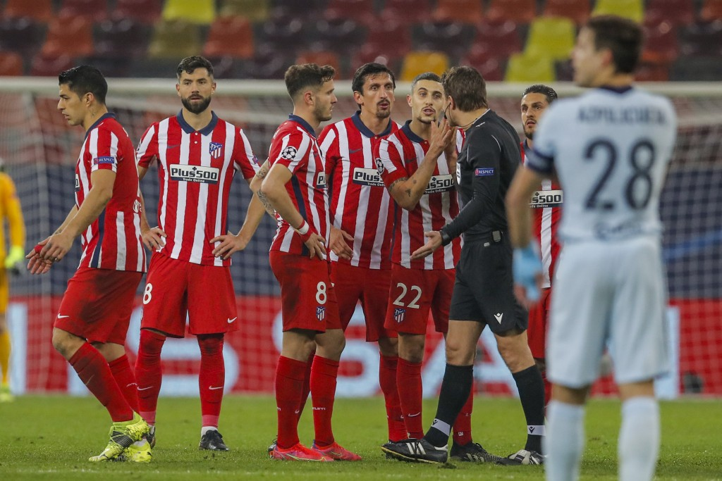 Atletico Madrid players talk with the referee during the Champions League, round of 16, first leg soccer match between Atletico Madrid and Chelsea at ...