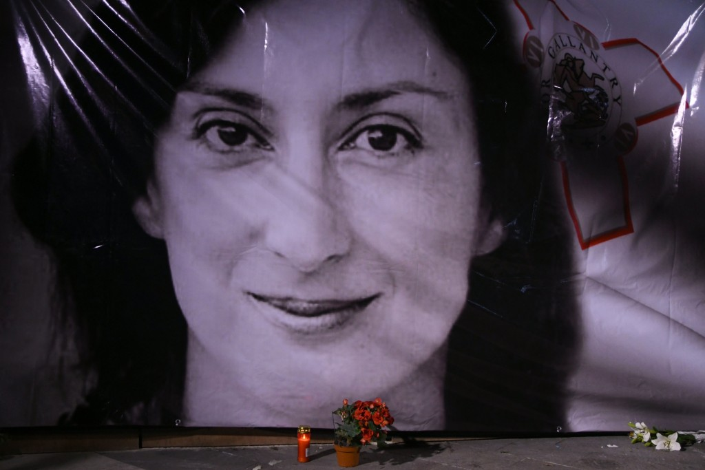 FILE - In this Tuesday, Oct. 16, 2018 file photo, flowers and a candle lie in front of a portrait of slain investigative journalist Daphne Caruana Gal...