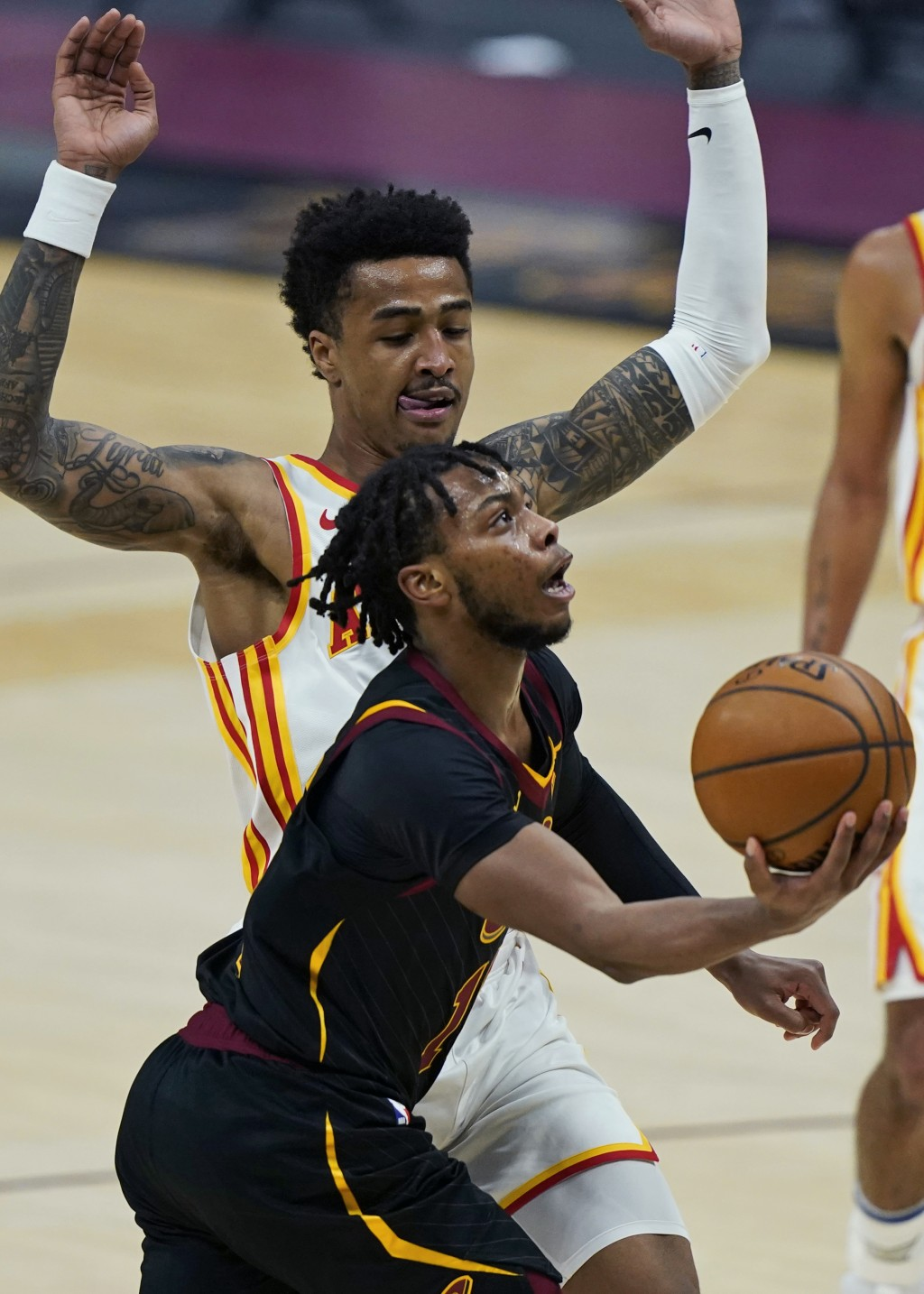 Cleveland Cavaliers' Darius Garland, front, drives to the basket against Atlanta Hawks' John Collins in the first half of an NBA basketball game, Tues...